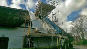 thatched roof cottage in scaffolding